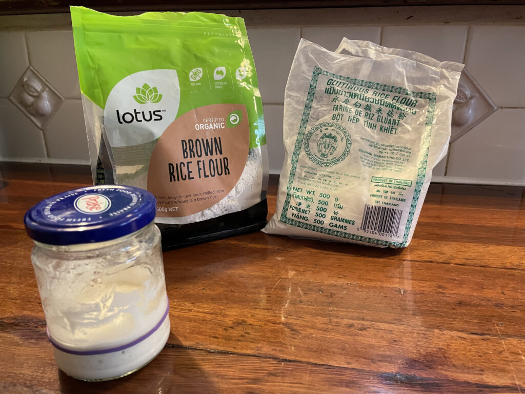 a jar with sourdough starter and in the background is a bag of brown rice flour and a bag of glutinous rice flour