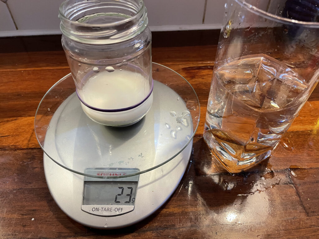 23 grams of water measured into the glass jar with the remaining water in a glass nearby